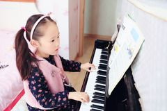 Little girl playing the piano at home. Little girl playing the grand piano at home ,Young girl sitting at a piano keyboard Stock Photo