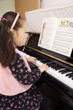 Little girl playing the piano at home. Little girl playing the grand piano at home ,Young girl sitting at a piano keyboard Royalty Free Stock Photography