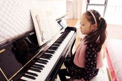 Little girl playing the piano at home. Little girl playing the grand piano at home ,Young girl sitting at a piano keyboard Royalty Free Stock Image