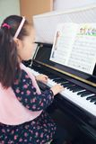 Little girl playing the piano at home. Little girl playing the grand piano at home ,Young girl sitting at a piano keyboard Royalty Free Stock Photo