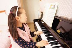 Little girl playing the piano at home. Little girl playing the grand piano at home ,Young girl sitting at a piano keyboard Stock Images