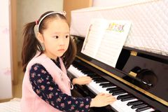 Little girl playing the piano at home. Little girl playing the grand piano at home ,Young girl sitting at a piano keyboard Stock Photos