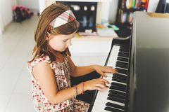 Little girl portrait. Little girl playing piano at home Royalty Free Stock Images