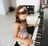 Little girl portrait. Little girl playing piano at home Stock Photo