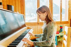 Portrait of adorable little girl playing piano Stock Images