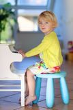 Little girl playing piano indoors Stock Photo