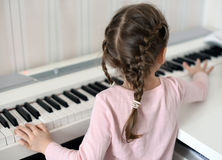 A little girl playing the piano: look from the back royalty free stock photography