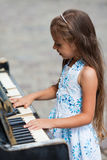 Little girl playing on a piano Royalty Free Stock Photos