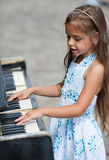 Little girl playing on a piano Royalty Free Stock Photography