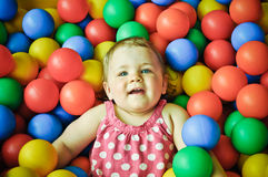 Little girl playing in plastic balls. Smiling one year old girl swimming in colourful plastic ball pool Royalty Free Stock Images