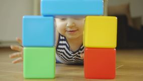 Little girl playing plastic toy cubes in a children`s room