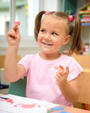 Little girl is playing with plasticine Stock Image