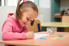 Little girl is playing with plasticine. In preschool Royalty Free Stock Image