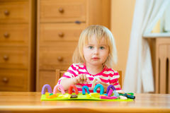 Little girl playing with plasticine. Cute Little girl playing with plasticine at home Royalty Free Stock Photos