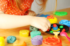 Little girl playing with plasticine. Four years old girl playing with plasticine in her room Royalty Free Stock Photos