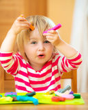 Little girl playing with plasticine. Funny little girl playing with plasticine at home Stock Images