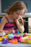 Little girl playing with plasticine at home Stock Image