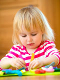 Little girl playing with plasticine. At home Royalty Free Stock Photo