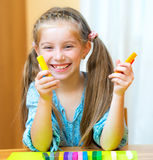 Little girl playing with plasticine. At home Stock Photography