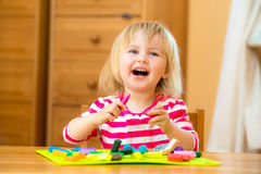 Little girl playing with plasticine. Laughing llittle girl playing with plasticine at home Royalty Free Stock Photography