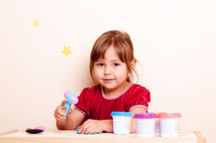 Little girl playing with plasticine. Little girl sculpting with plasticine in school Royalty Free Stock Image