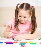 Little girl is playing with plasticine. While sitting at table Stock Photo