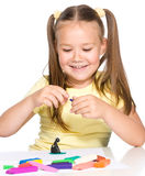 Little girl is playing with plasticine. While sitting at table,  over white Stock Photos