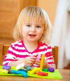 Little girl playing with plasticine. Smiling Little girl playing with plasticine at home Royalty Free Stock Image