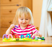 Little girl playing with plasticine. Smiling girl playing with plasticine at home Stock Photography