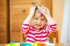 Little girl playing with plasticine. Smiling girl playing with plasticine at home Royalty Free Stock Photos