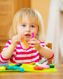 Little girl playing with plasticine Stock Images