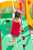 Little girl playing on playground, climbing the wall on rope Stock Images
