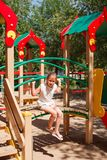 Little girl is playing at playground. Cute blonde little girl is playing at playground. She is sitting on the little bridge Stock Photography