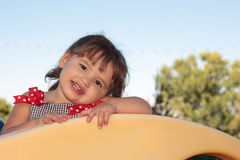 Little Girl Playing on Playground Equipment. Cute toddler girl with pigtails playing on playground equipmant Royalty Free Stock Photography