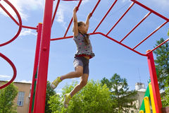 Little girl playing on a playground, hanging walk along the monkey bars Stock Image