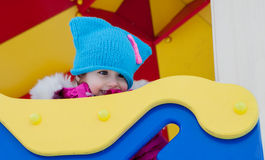 Little girl playing on the Playground, having fun playing spinning the day of the winter on the street in the Park.  Stock Photo
