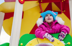 Little girl playing on the Playground, having fun playing spinning the day of the winter on the street in the Park.  Stock Photography