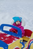 Little girl playing on the Playground, having fun playing spinning the day of the winter on the street in the Park.  Royalty Free Stock Photography