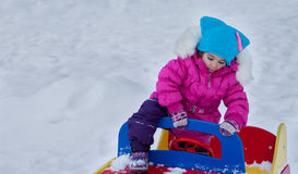Little girl playing on the Playground, having fun playing spinning the day of the winter on the street in the Park.  Royalty Free Stock Images