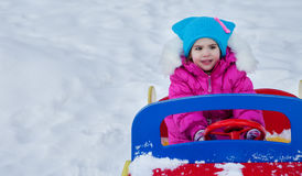 Little girl playing on the Playground, having fun playing spinning the day of the winter on the street in the Park.  Royalty Free Stock Image