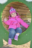 A little girl playing on the playground and laughs. Royalty Free Stock Image