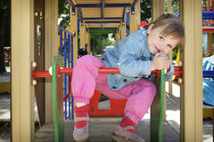 A little girl playing on the playground and laughs. Royalty Free Stock Photography