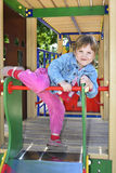 A little girl playing on the playground and laughs. Stock Photo