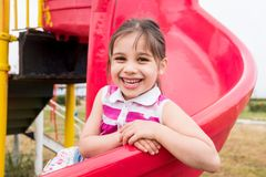 Little Girl Playing At Playground Outdoors In Summer stock photography