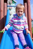 Little girl playing on a playground slide Stock Images