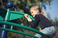 Little girl playing on playground. Stock Photos