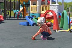 Little girl playing on the Playground on a warm Sunny day royalty free stock photography