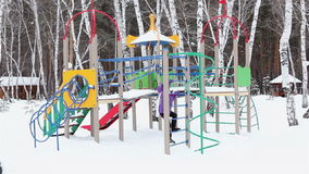 Little girl playing on playground in winter. Stock Image