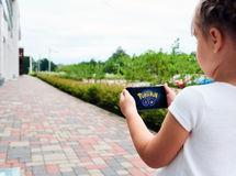 Little girl playing a Pokemon Go game outdoors. Stock Images