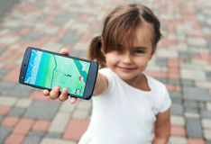 Little girl playing a Pokemon Go game outdoors. Riga, Latvia- July 17, 2016: Little girl playing a Pokemon Go game outdoors. Pokemon Go is a popular virtual Royalty Free Stock Images